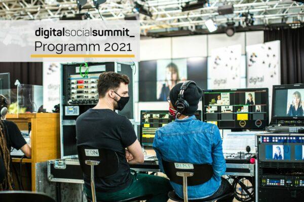 Es ist eine Studioszene zu sehen. Zwei Techniker sitzen nebeneinander vor Monitoren und Schaltpulten. Beide tragen eine Maske und scheinen in ein Gespräch vertieft zu sein. Im Hintergrund ist das Studioset des Digital Social Summits 2020 zu sehen. Oben rechts steht das Logo des Digital Social Summits und Programm 2021.