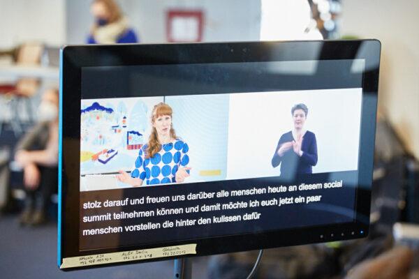 Dreigeteilter Bildschirm auf dem die Moderatorin, eine Gebärdensprachdolmetscherin und Untertitel zu sehen sind.